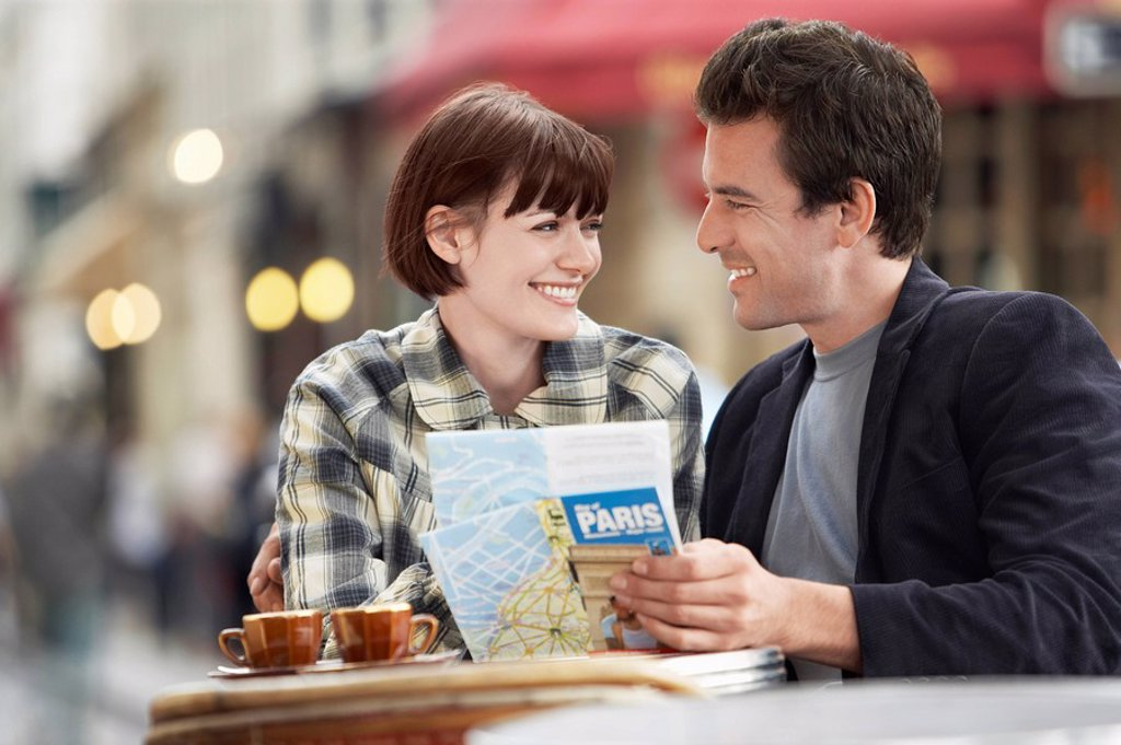 Stock Photo: 1654R-10643 France Paris Couple reading map sitting outside cafe