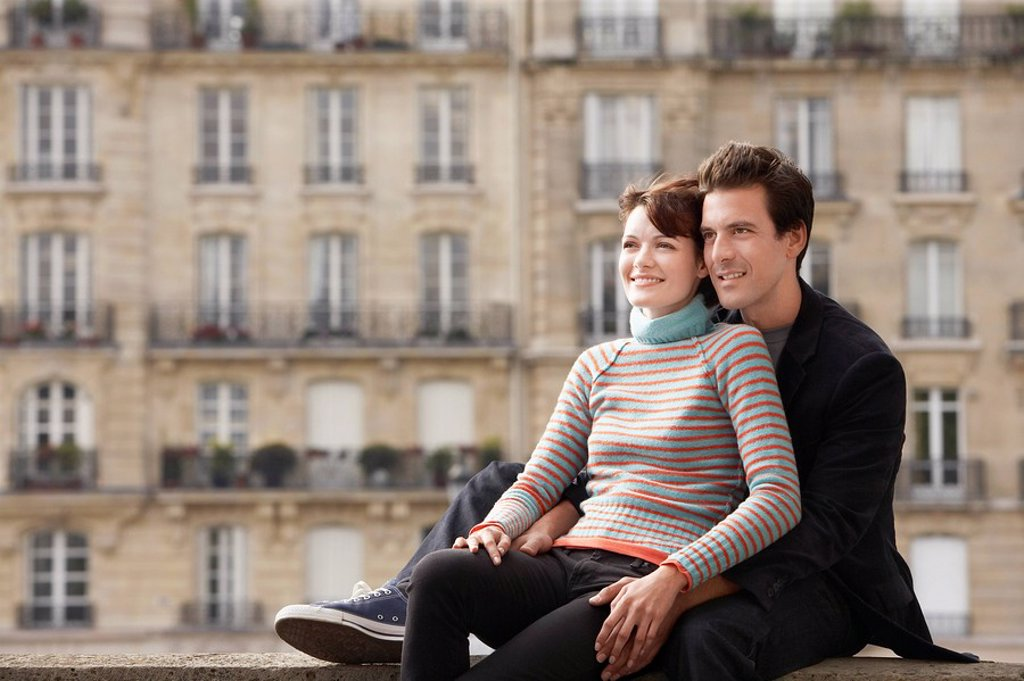 Young couple posing on bridge in front of town houses : Stock Photo