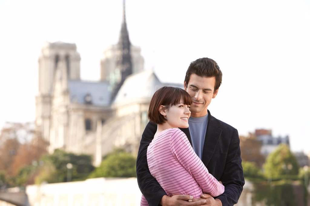 Stock Photo: 1654R-10653 Paris France Couple embracing in front of Notre Dame Cathedral