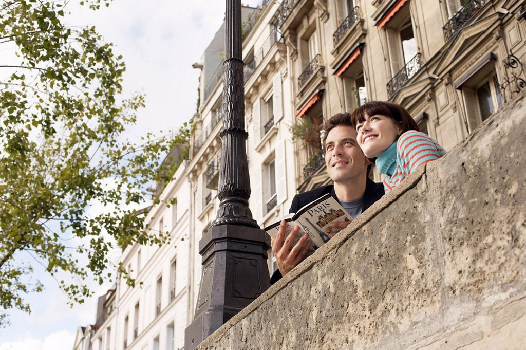 France Paris Couple looking over bridge with guidebook : Stock Photo