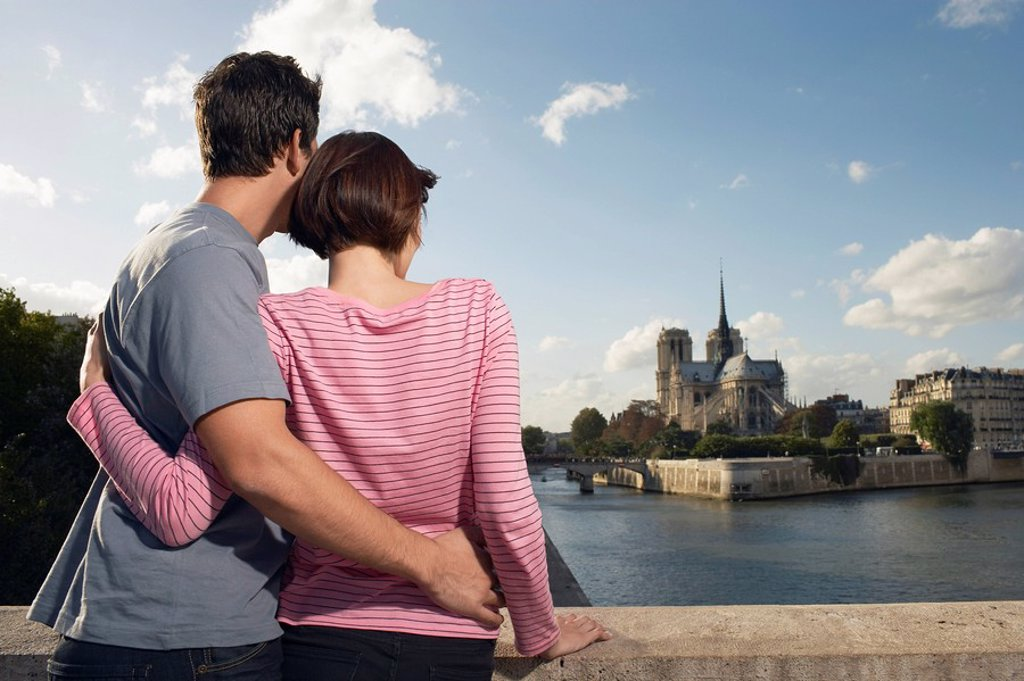 Stock Photo: 1654R-10658 Paris France Couple embracing in front of Notre Dame Cathedral back view