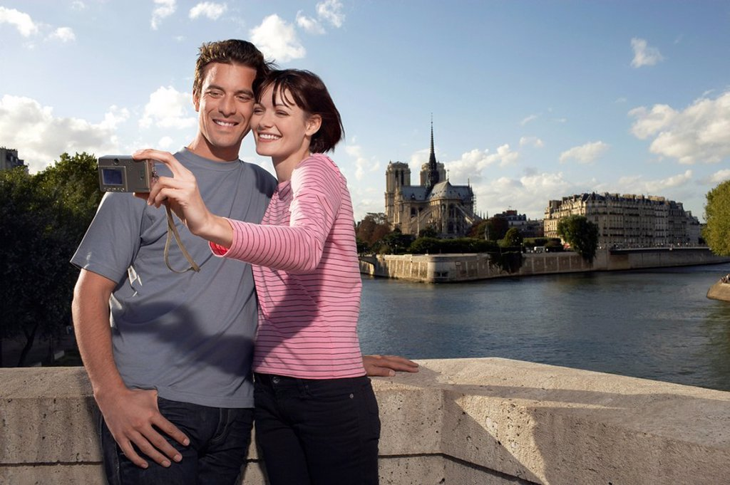 Paris France Couple taking a photo of themselves in front of Notre Dame Cathedral : Stock Photo