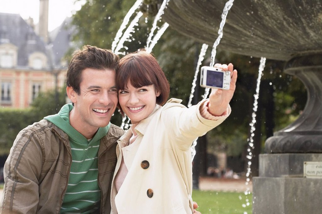 Couple photographing themselves in front of fountain : Stock Photo