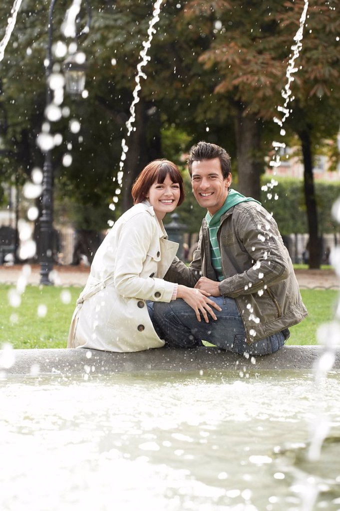 Stock Photo: 1654R-10668 Couple sitting on edge of fountain view past water jets