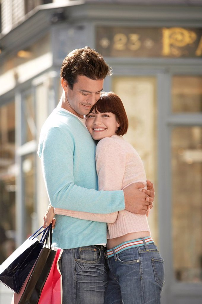 Couple with shopping bags embracing on street corner : Stock Photo