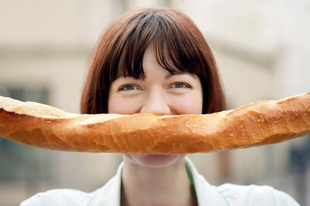 Woman Holding Baguette in Front of Face head and shoulders : Stock Photo