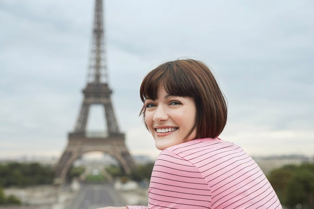 Stock Photo: 1654R-10696 France Paris Young woman smiling with Eiffel Tower in distance
