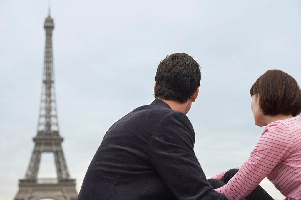 Stock Photo: 1654R-10697 France Paris Couple looking at Eiffel Tower back view