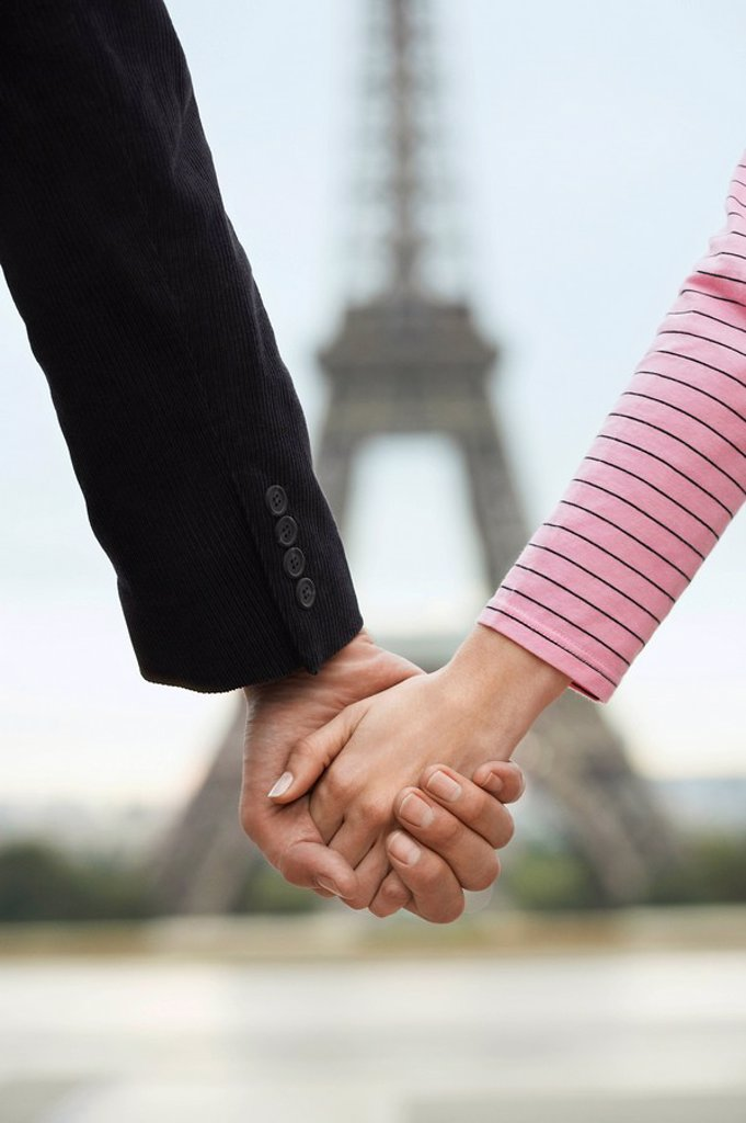 France Paris Couple holding hands in front of Eiffel Tower close up of hands : Stock Photo