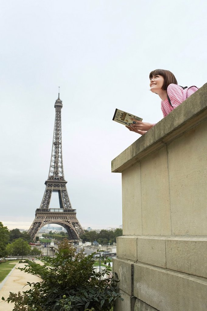 France Paris Young woman reading book on balcony in front of Eiffel Tower : Stock Photo