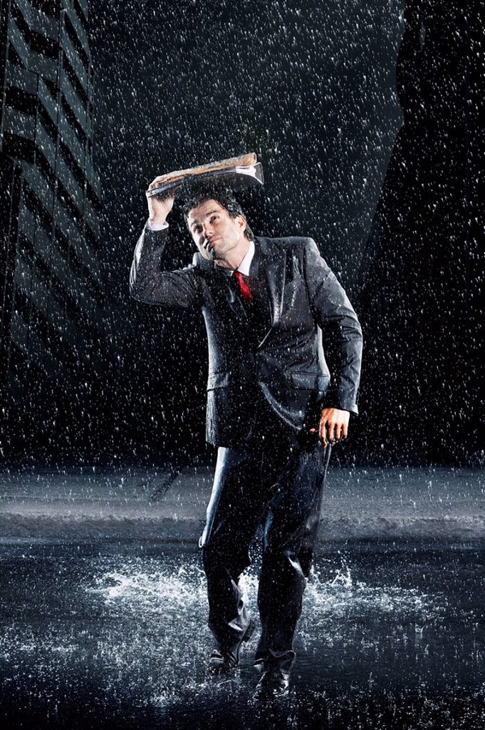 Businessman covering head with binder running through rain : Stock Photo
