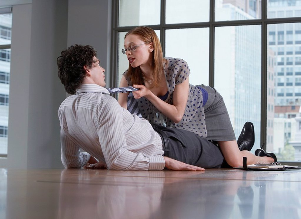 Stock Photo: 1654R-10802 Woman seducing man on office floor