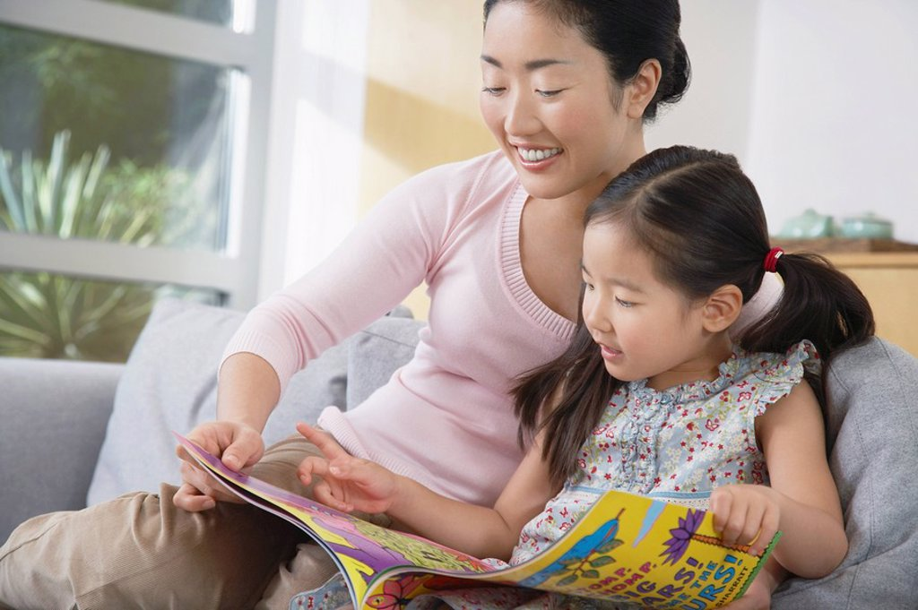 Mother sitting with daughter on sofa reading a book : Stock Photo
