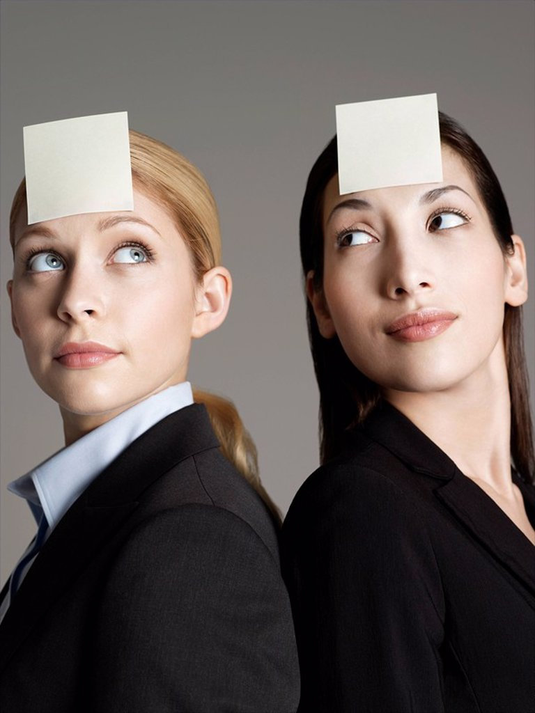 Portrait of two female office workers with sticky notes on forehead : Stock Photo