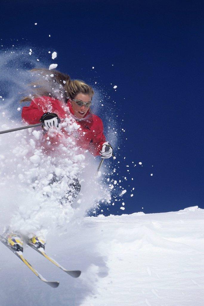 Stock Photo: 1654R-11258 Skier skiing through powdery snow on ski Slope