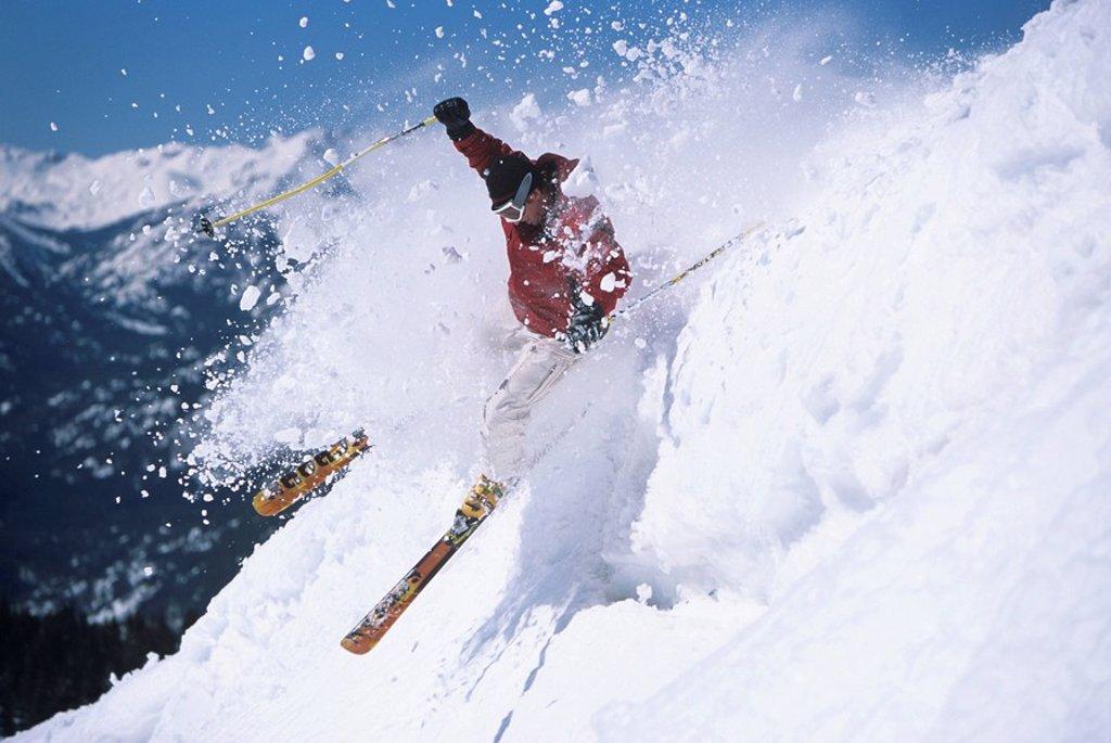 Skier skiing through powdery snow on ski Slope : Stock Photo