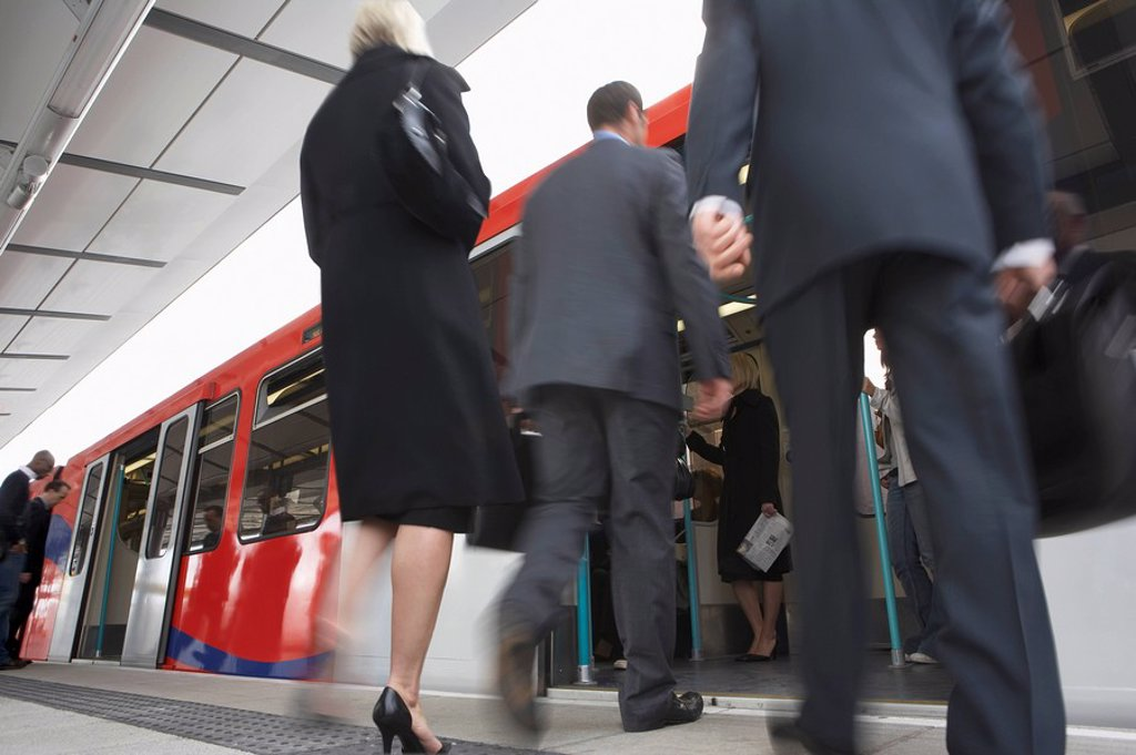 Business Commuters Getting on Train motion blur low angle view : Stock Photo