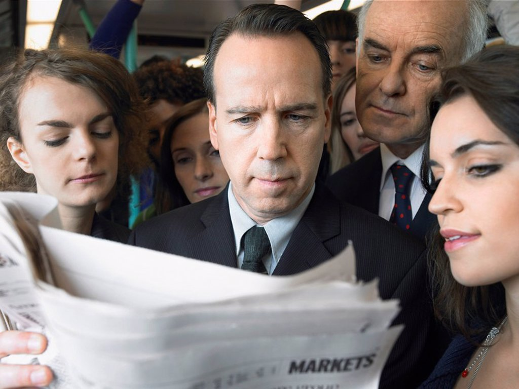 Commuters standing on train reading newspaper over shoulder : Stock Photo