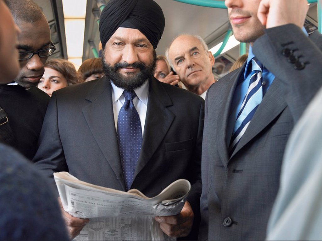 Commuter in turban Reading paper on Train : Stock Photo
