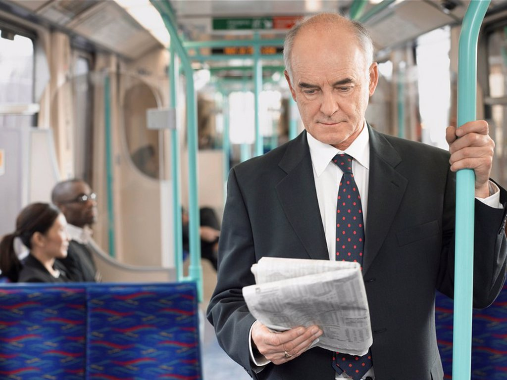 Businessman Reading Newspaper on Train holding onto bar : Stock Photo