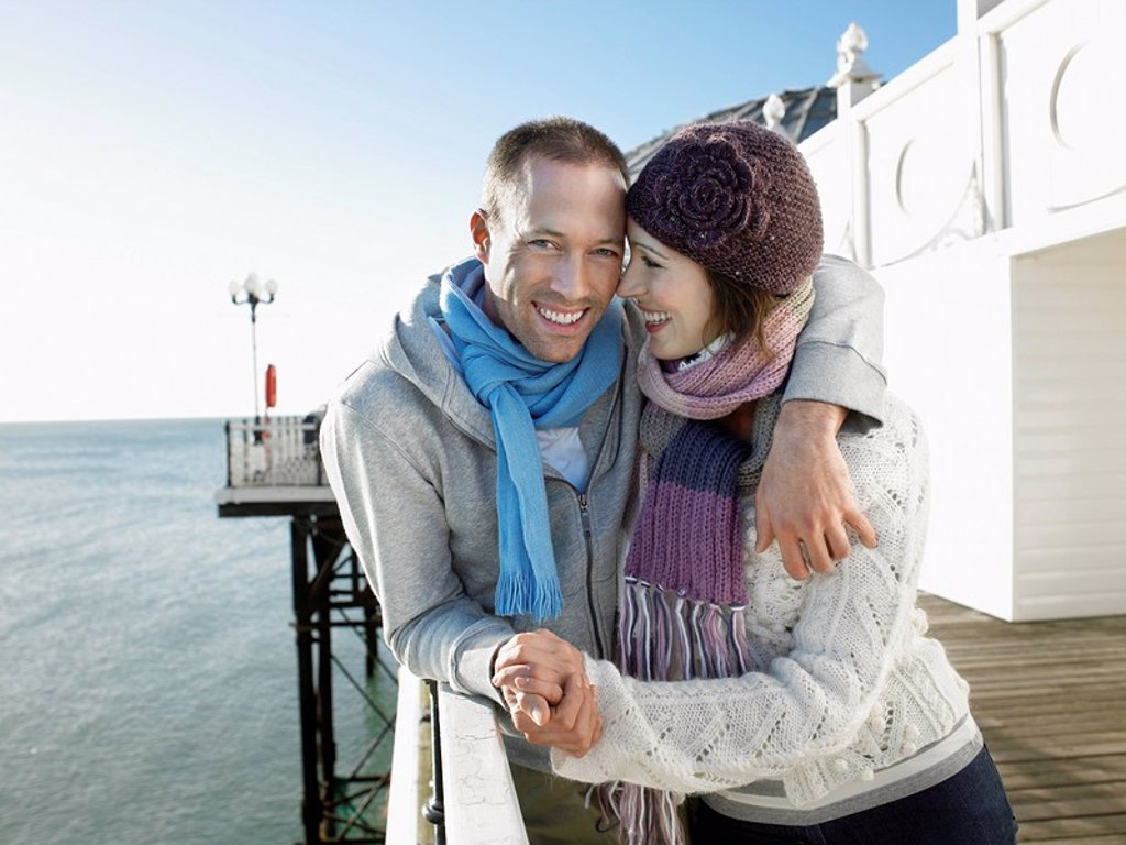 Couple holding hands standing on pier portrait : Stock Photo