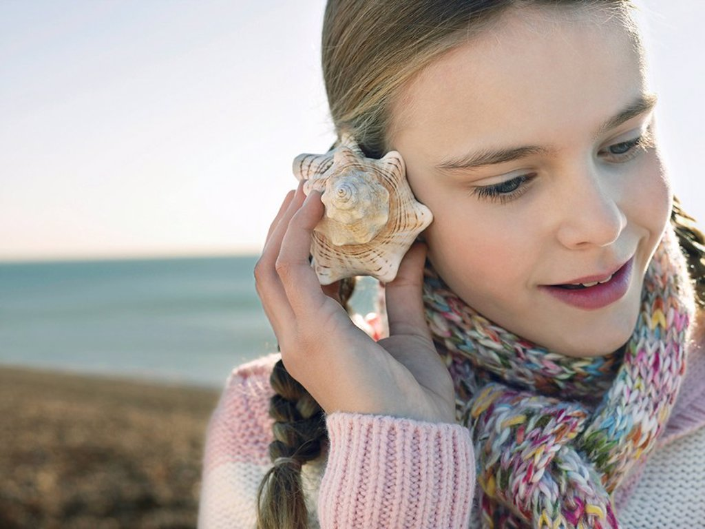 Pre teen girl listening to seashell standing on beach close up : Stock Photo