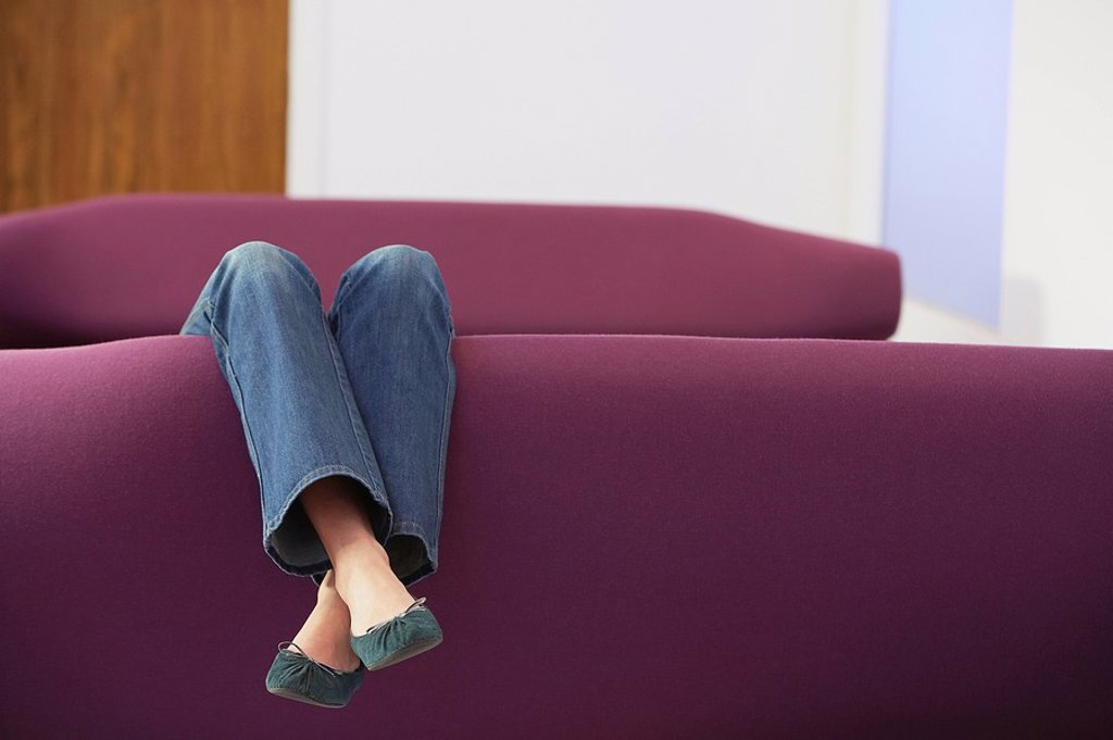 Woman Relaxing upside down on Sofa low section : Stock Photo
