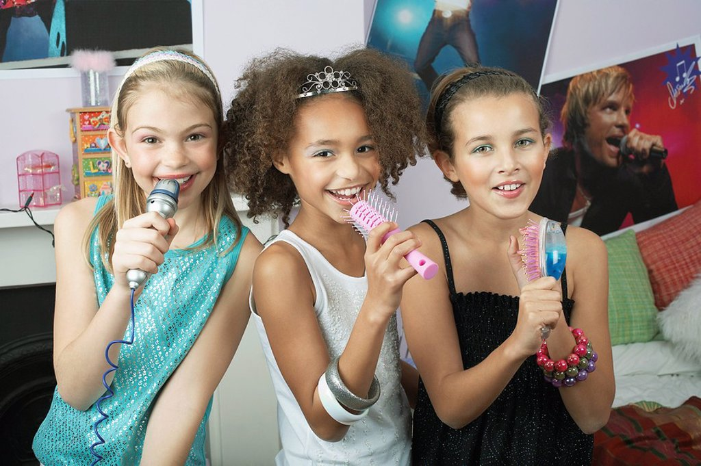 Girls using brushes microphones to sing at a Slumber Party : Stock Photo