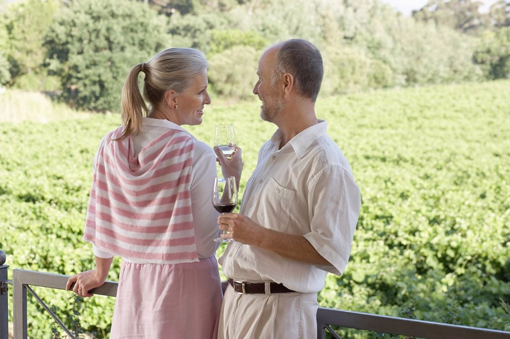 Mature couple on terrace holding wine glasses : Stock Photo