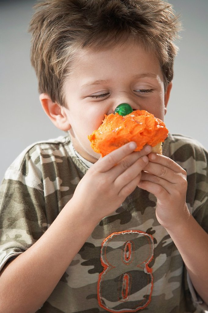 Young boy eating cupcake half length : Stock Photo