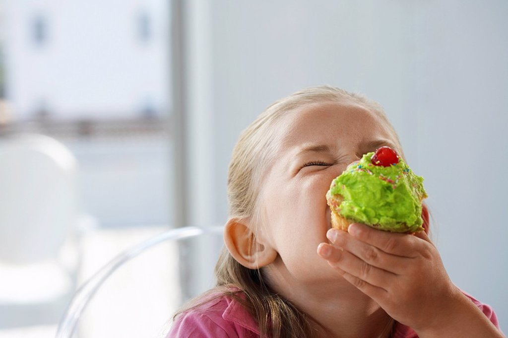 Stock Photo: 1654R-11785 Young girl eating cupcake head and shoulders
