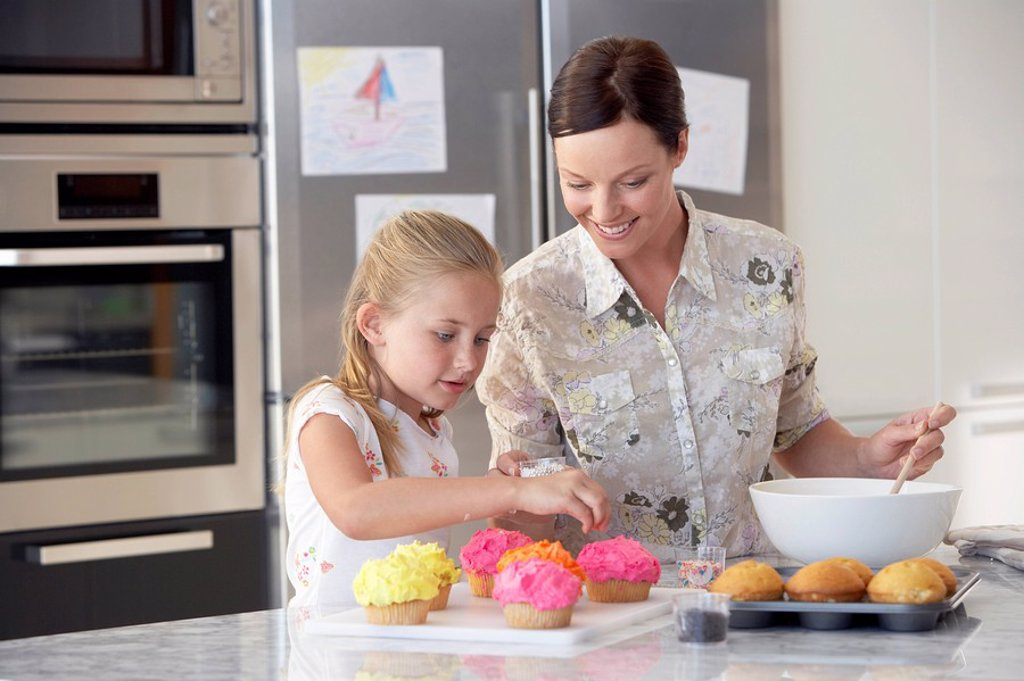 Mother and Daughter Making Cupcakes in kitchen : Stock Photo