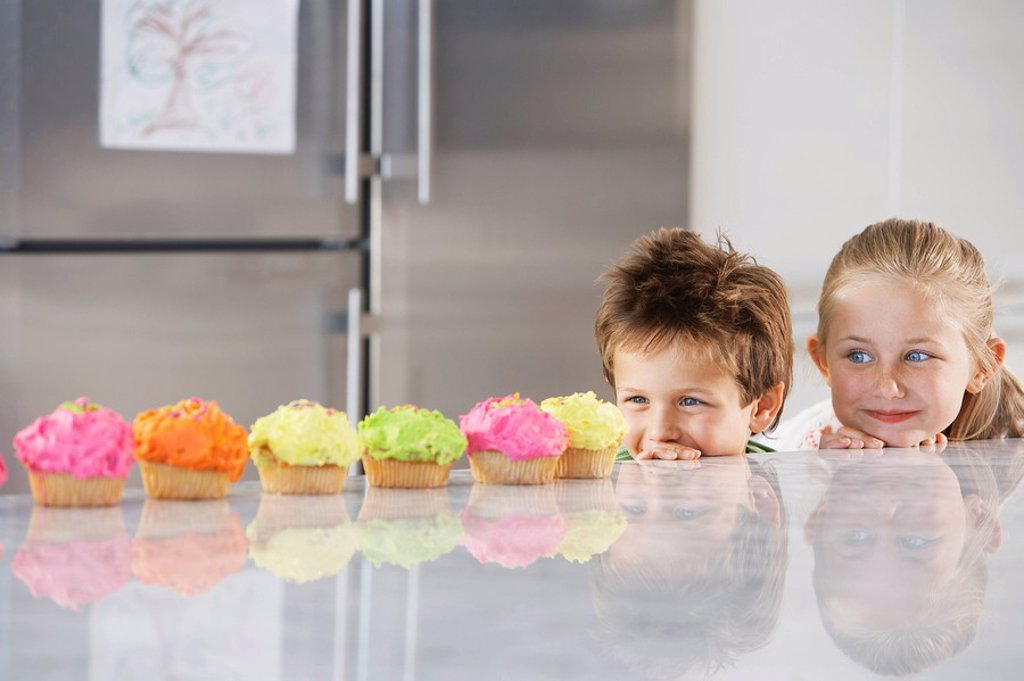 Young girl and boy looking over counter at row of cupcakes in kitchen : Stock Photo