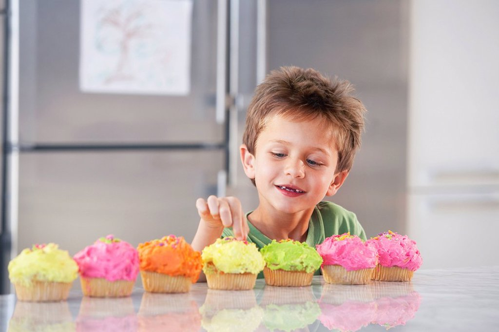 Young boy picking decoration off cupcake in kitchen : Stock Photo