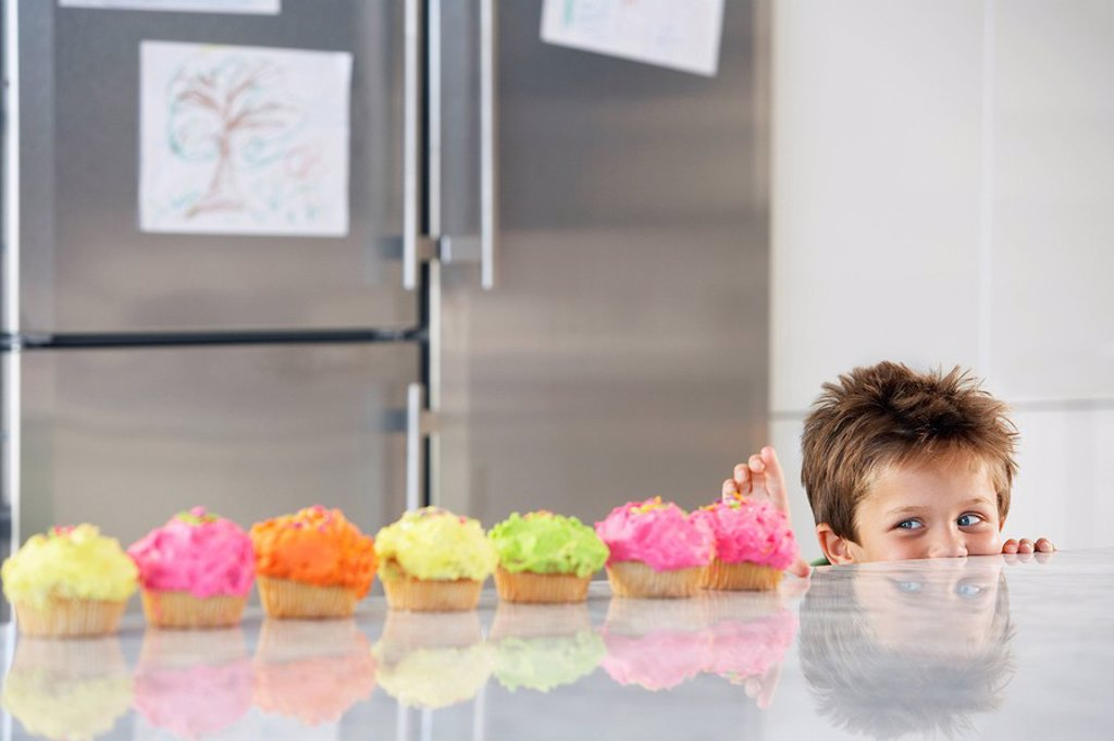 Young boy peaking over counter at row of cupcakes in kitchen : Stock Photo