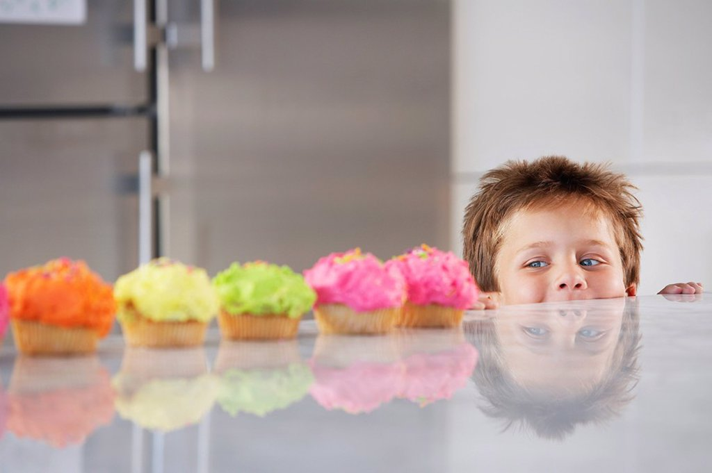 Young boy peeking over counter at row of cupcakes in kitchen : Stock Photo