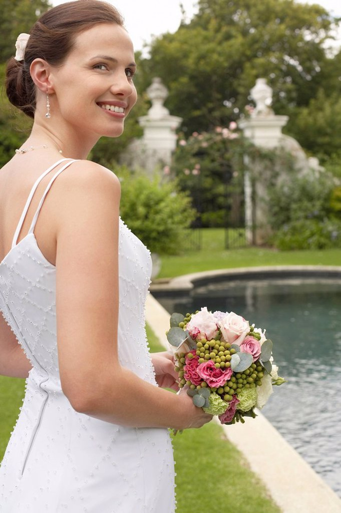 Mid adult bride at poolside holding bouquet looking over shoulder : Stock Photo