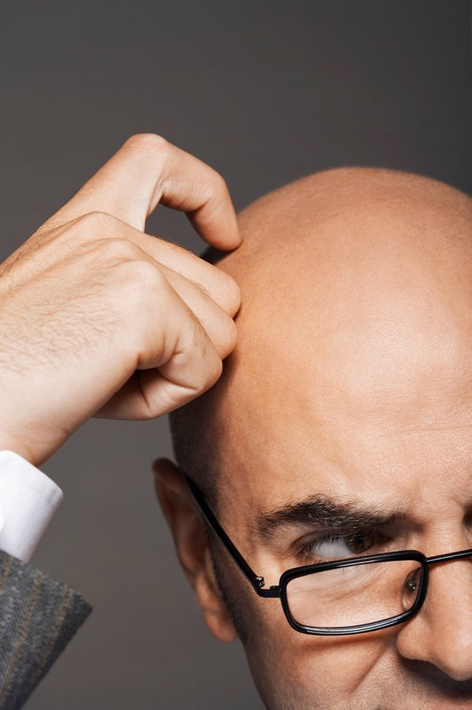 Stock Photo: 1654R-11978 Bald businessman wearing glasses scratching head high section
