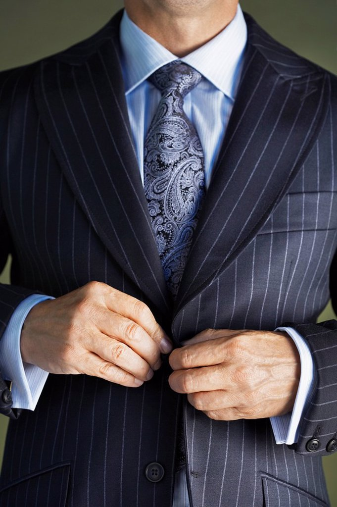 Stock Photo: 1654R-11999 Middle_aged businessman in full suit buttoning buttons on jacket mid section