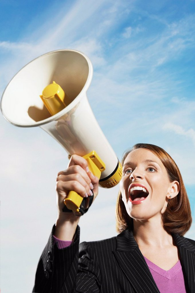 Smiling Mid_adult woman shouting through megaphone outside : Stock Photo