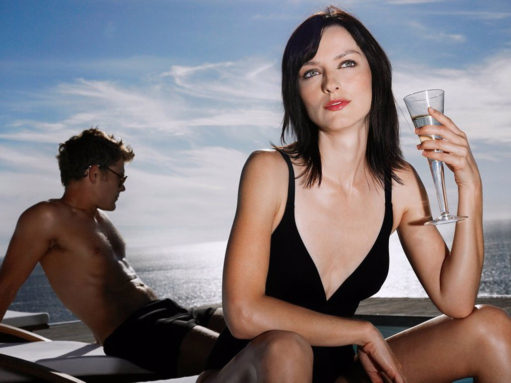 Woman holding champagne glass man relaxing near sea : Stock Photo
