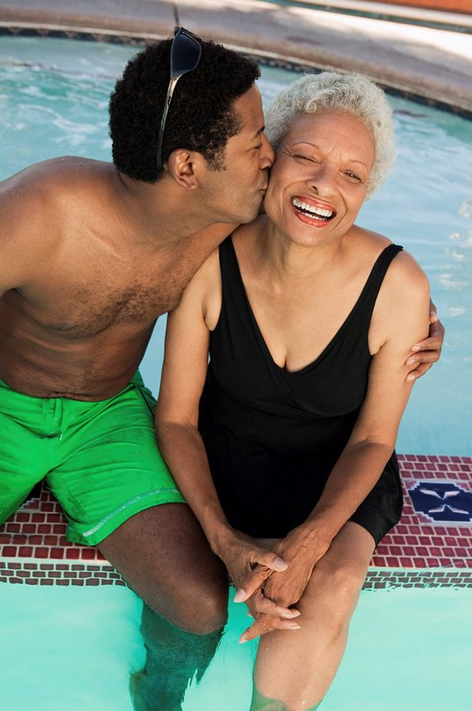Man sitting on edge of swimming pool kissing mother on cheek elevated view. : Stock Photo