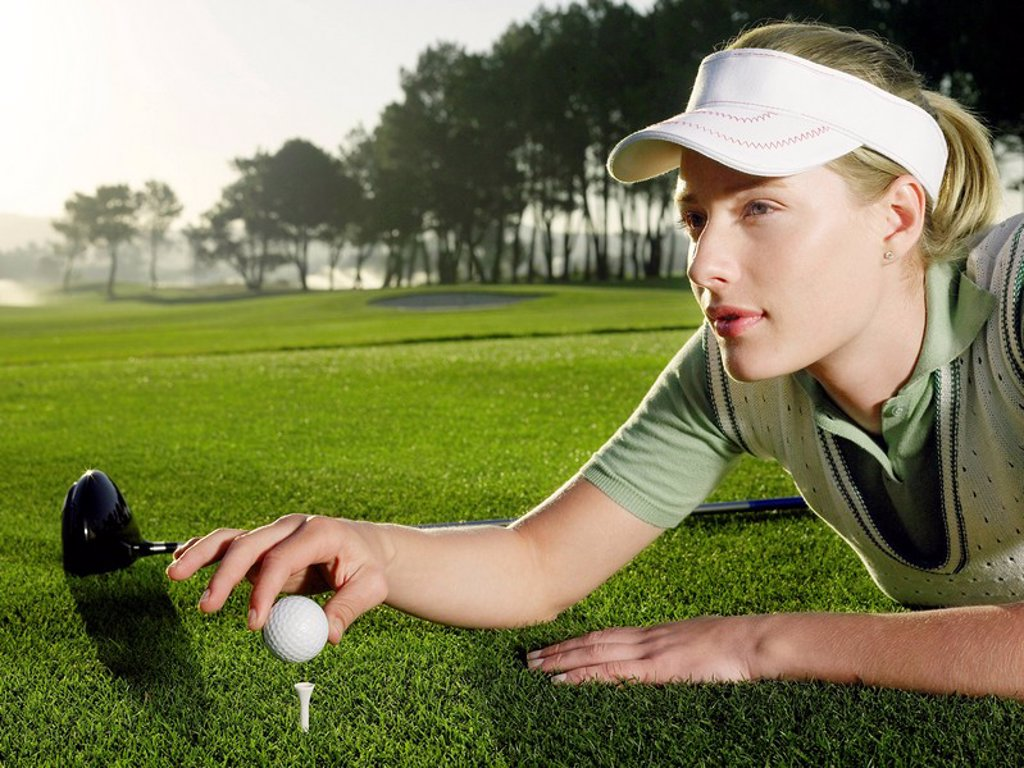 Stock Photo: 1654R-12445 Young female golfer lying on court placing ball on tee