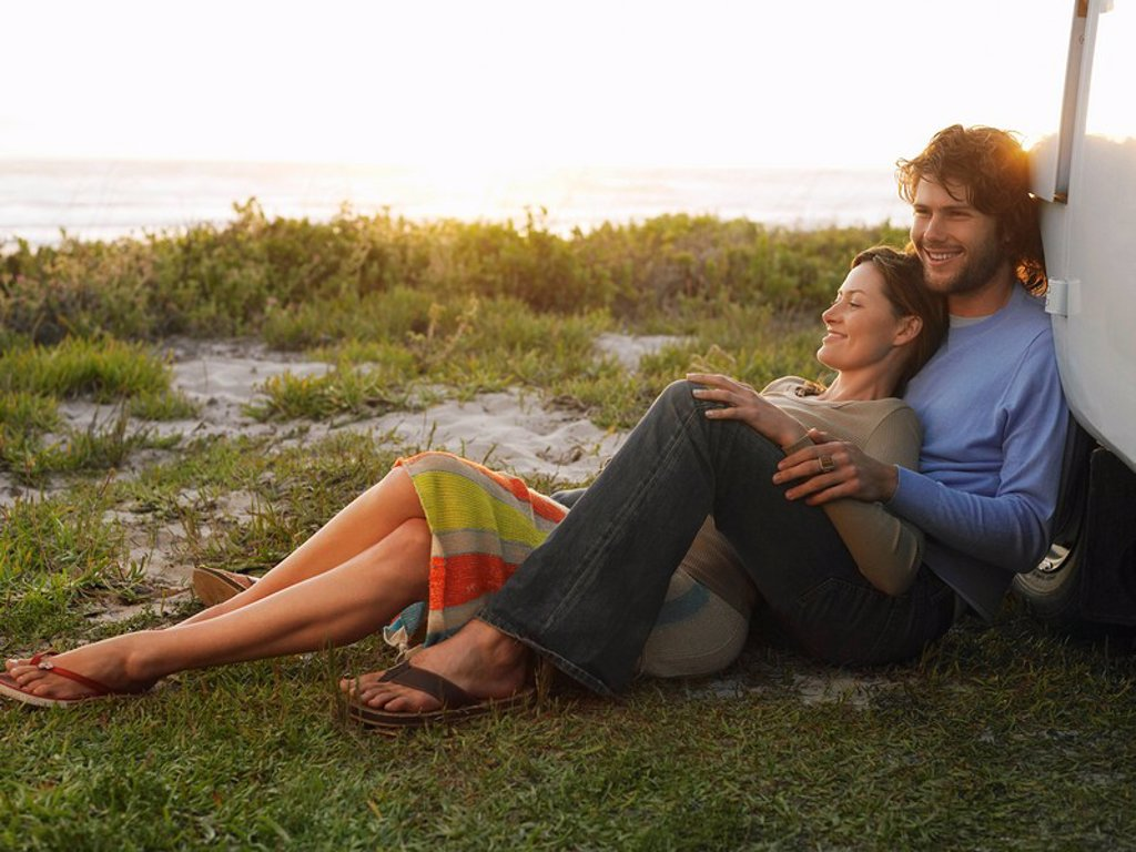 Couple leaning against van wheel van parked on cliff above ocean : Stock Photo
