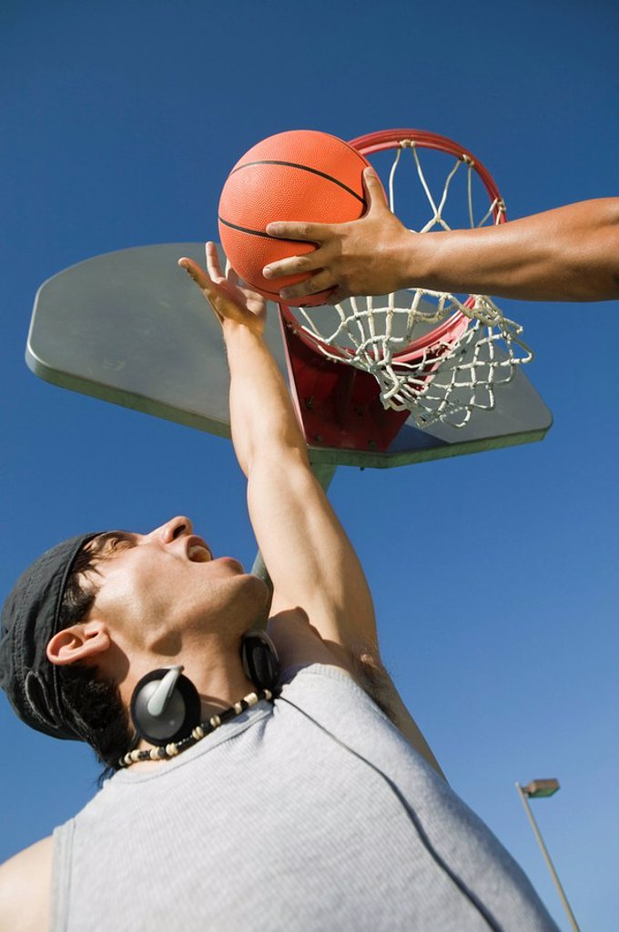 Stock Photo: 1654R-1254 Two men playing basketball low angle view.
