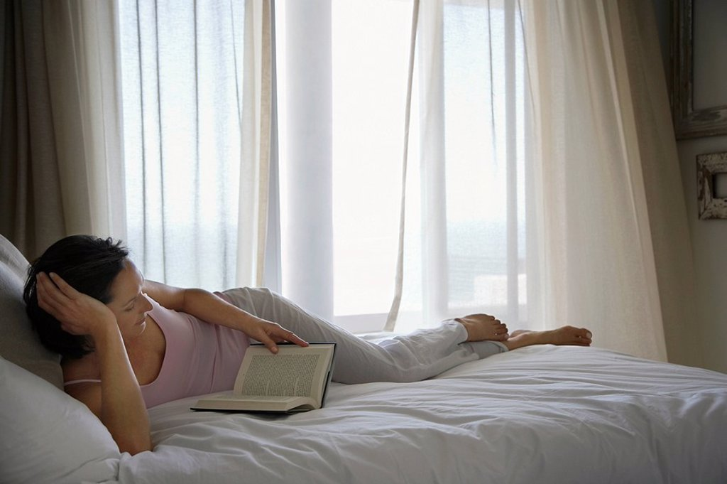 Stock Photo: 1654R-12561 Woman reading book lying on bed