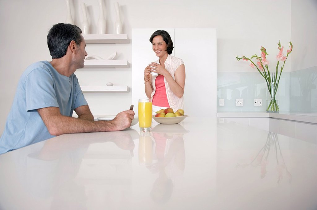Couple having breakfast at kitchen bench : Stock Photo