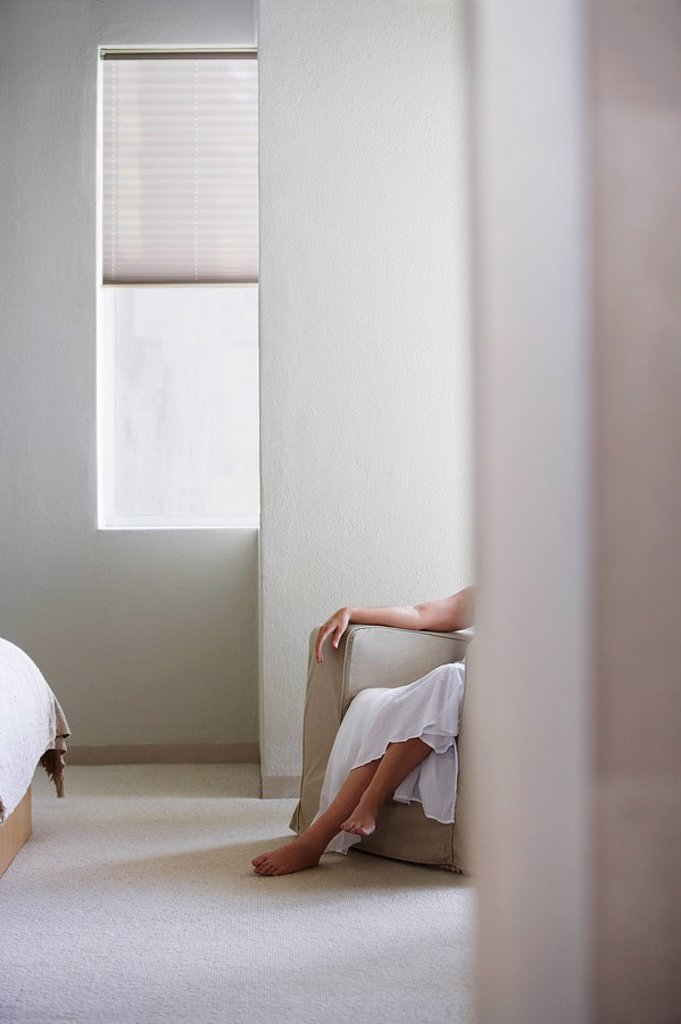 Stock Photo: 1654R-12648 Woman sitting on armchair in bedroom low section