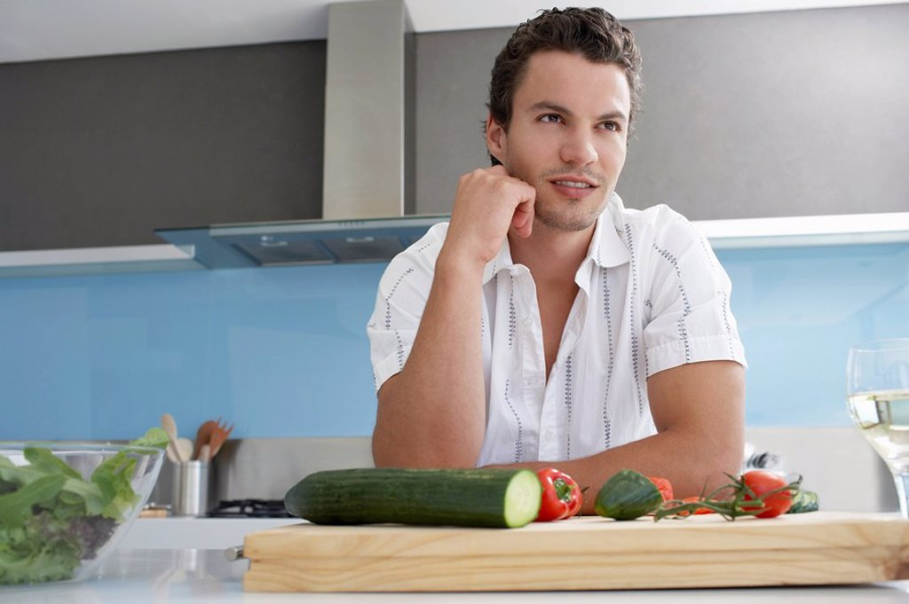 Young man leaning on kitchen counter near cutting board with vegetables hand on chin : Stock Photo