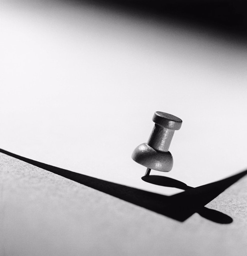 Stock Photo: 1654R-13062 Push pin holding down paper b&w close_up